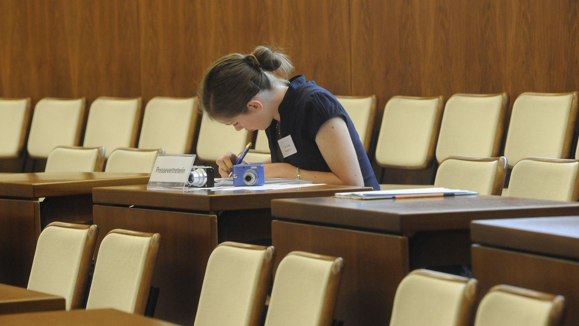 Eine Besucherin sitzt an einem Tisch im ehemaligen Bundesrat Bonn