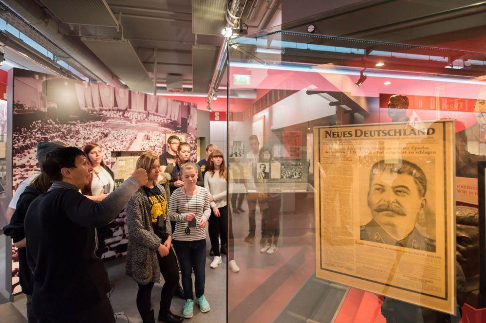 Begleiterin erklärt einer Gruppe etwas zu Stalin