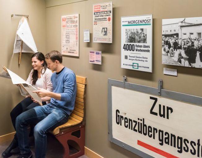 Besucher mit einer Zeitung im Bereich 'Grenzübergang' in der Dauerausstellung