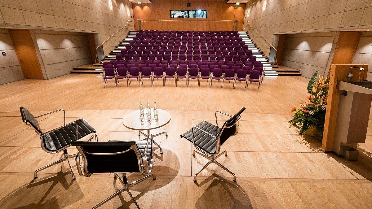 Blick von einer Bühne in einen großen Raum mit aufsteigenden Stuhlreihen.
