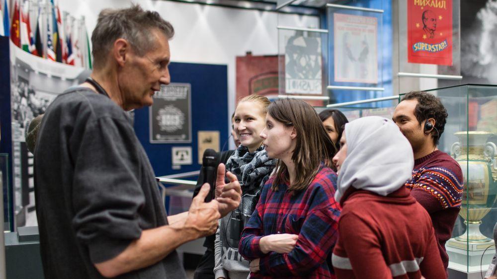 Ein älterer Mann im Sweatshirt steht mit Mikrofon  und fünf jungen Menschen unterschiedlicher Herkunft in der Ausstellung