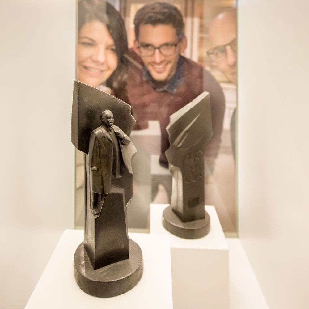 Two young men and a woman are looking at two small sculptures in a show case
