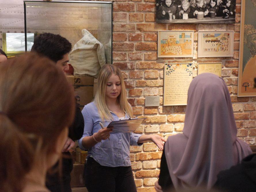 Mädchen erklärt eine Karikatur in der Dauerausstellung
