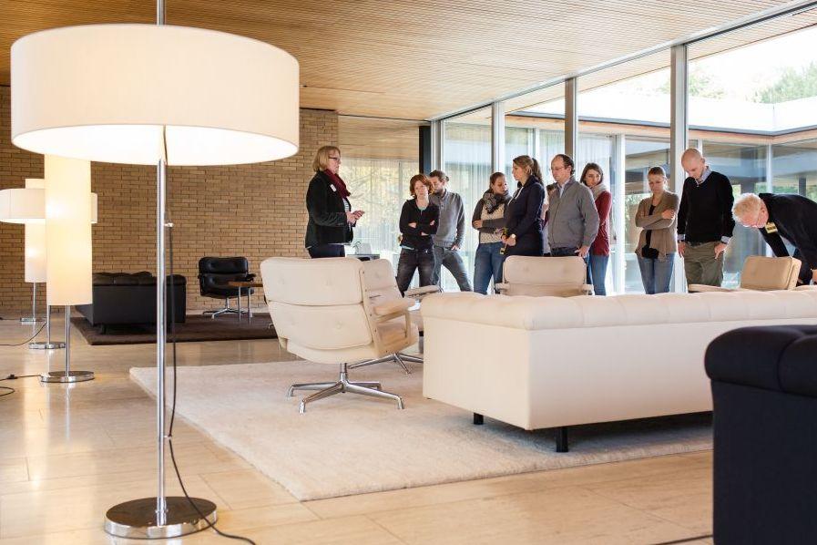 Blick in einen hellen Raum mit einer großen Lampe und großzügigen Sitzgarnituren, Holz- und Steinmaterialien sowie einer Glasfront. In dem Raum befindet sich eine Besuchergruppe