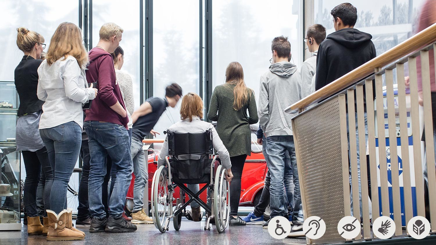 A group with a girl in a wheelchair during a guided tour through Haus der Geschichte museum.