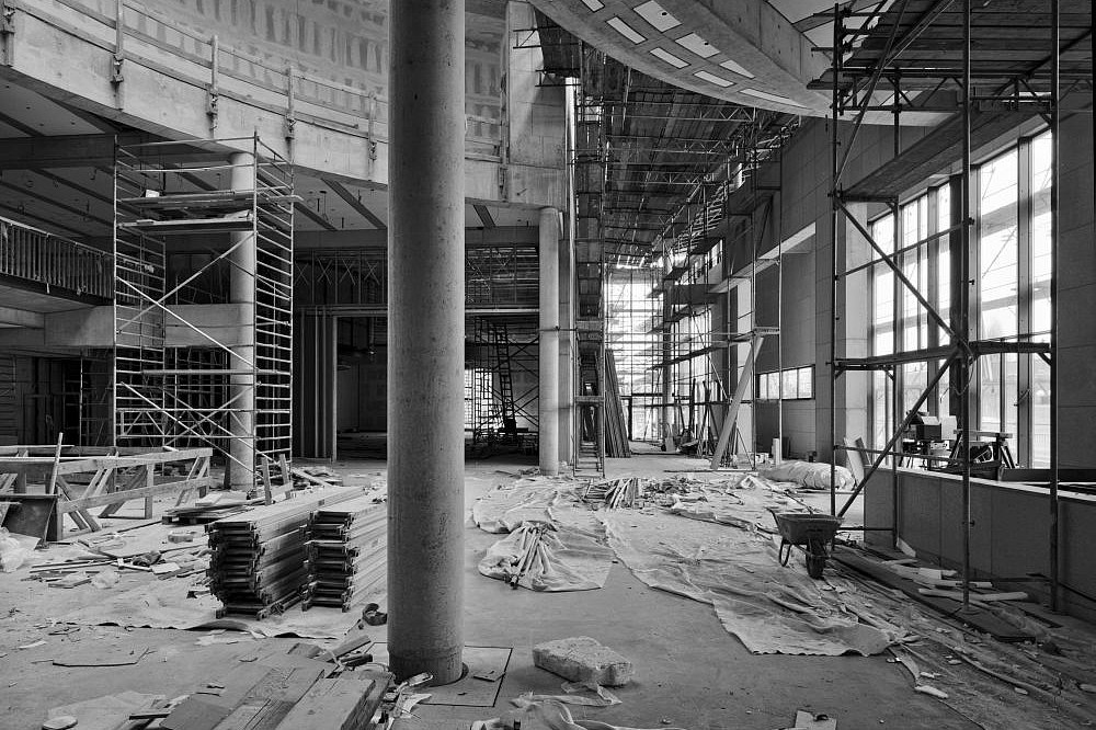 Schwarzweiß-Aufnahme des großzügigen Foyers mit Gerüsten und Baumaterialien