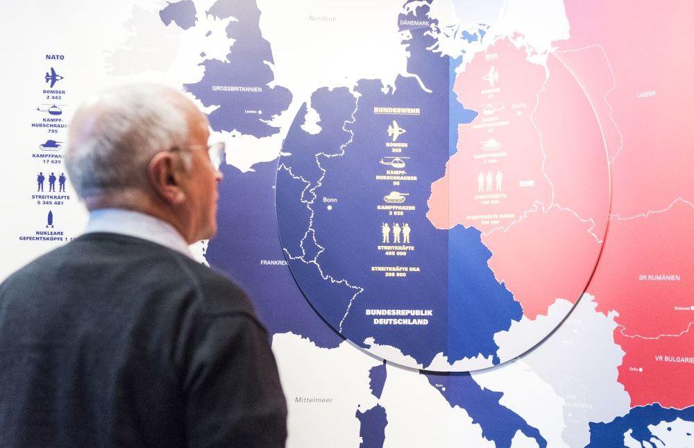 Ein Mann steht vor einer Europakarte, in der die UdSSR rot, die europäischen Staaten westlich davon blau eingefärbt sind
