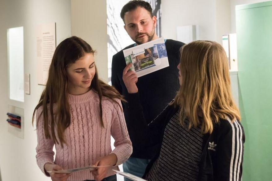 Zwei Besucherinnen und ein Besucher mit Familientour-Material