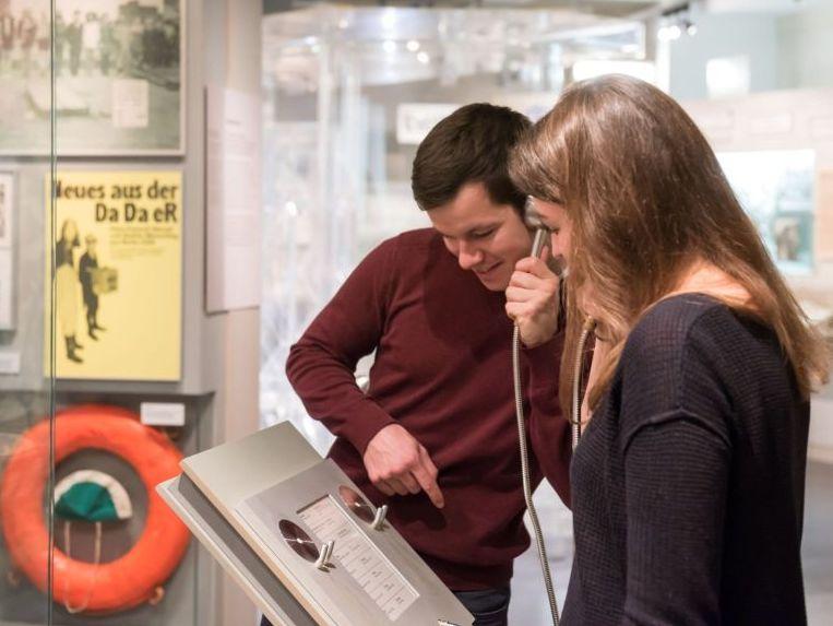 Eine Besucherin und eine Besucher benutzen eine Medienstation