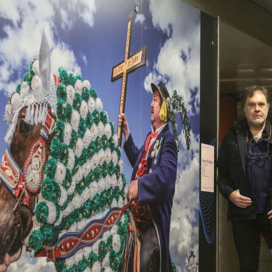 Im linken Teil des Bildes sieht man eine Fotografie von Hans-Jürgen Burkard, das ein Kaltblut mit Tracht zeigt. Rechts steht der Fotograf.