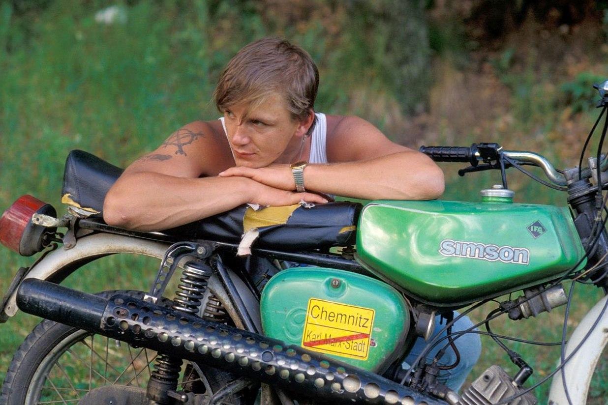 Ein junger Mann lehnt im Muskelshirt auf seinem Simson-Moped.