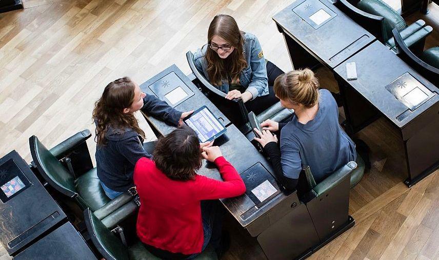 Junge Frauen mit Tablet sitzen auf dem historischen Bundestagsgestühl im Haus der Geschichte