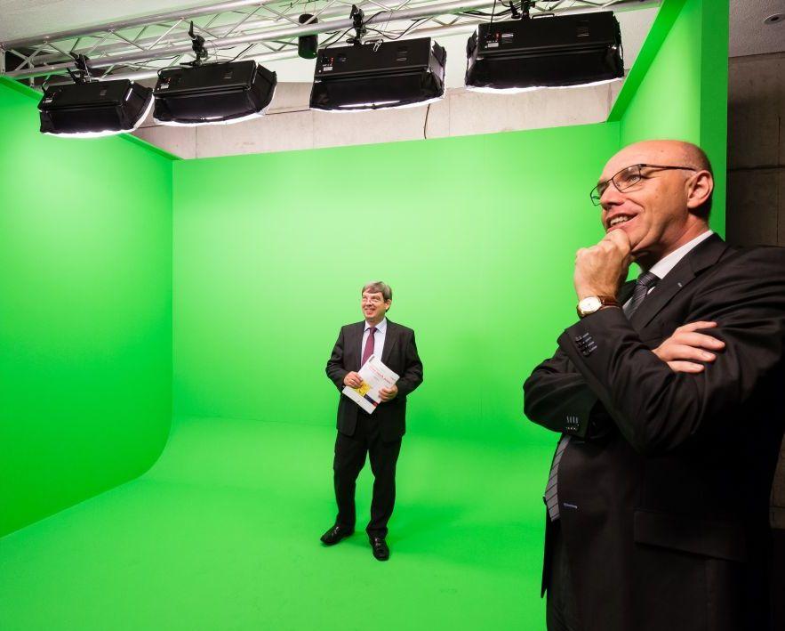 Ein Mann im Anzug steht in einer Green Box, einer grünen Raumeinheit, die nach vorne offen ist, und wird von vorne angestrahlt
