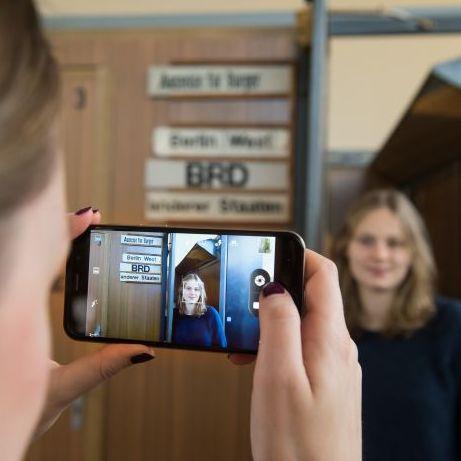 Eine Besucherin macht ein Foto von einem Mädchen in der Grenzkabine