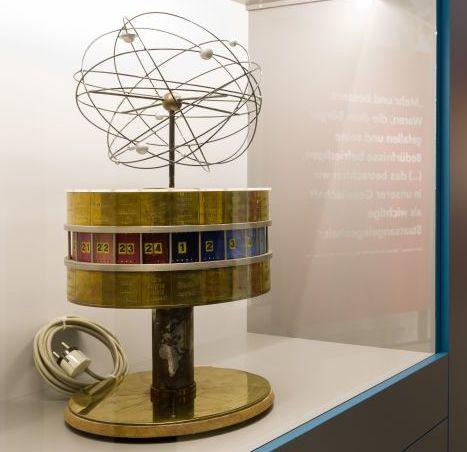 Blick in einen großen Ausstellungsraum, im Vordergrund das Modell der Weltzeituhr mit einem Zylinder auf einem Sockel und den Planeten unseres Sonnensystems mit ihrer Umlaufbahn