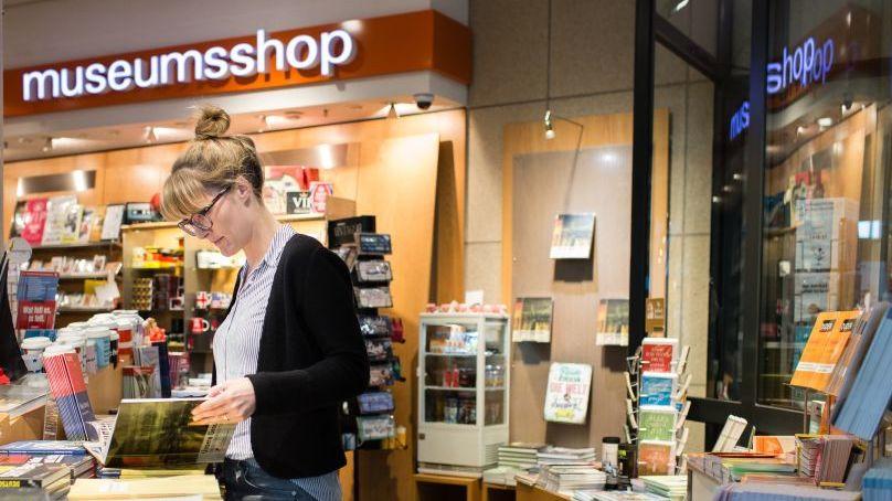 Eine Frau blättert im Buch zur Dauerausstellung im Museumsshop