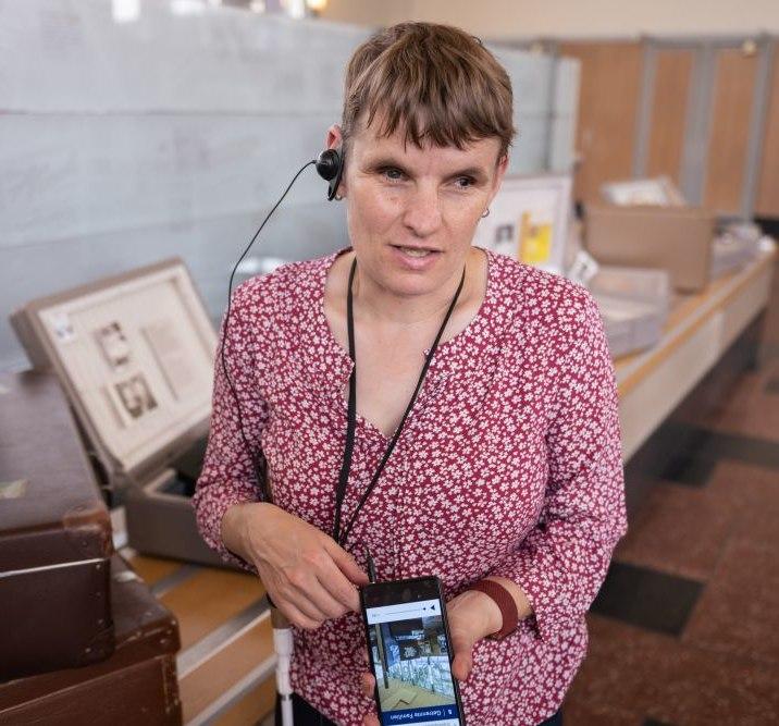 Eine Besucherin mit Seheinschränkung hört den AudioGuide mit Audiodeskription