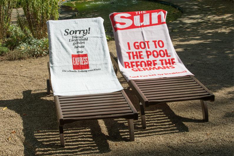 """Zwei Liegestühle mit Handtüchern, eines vom Express, """"Sorry, dieser LIegestuhl gehört heute mir!"""" und eines von der britischen Boulevardzeitung """"The Sun"""", """"I got to the pool before the Germans""""."""