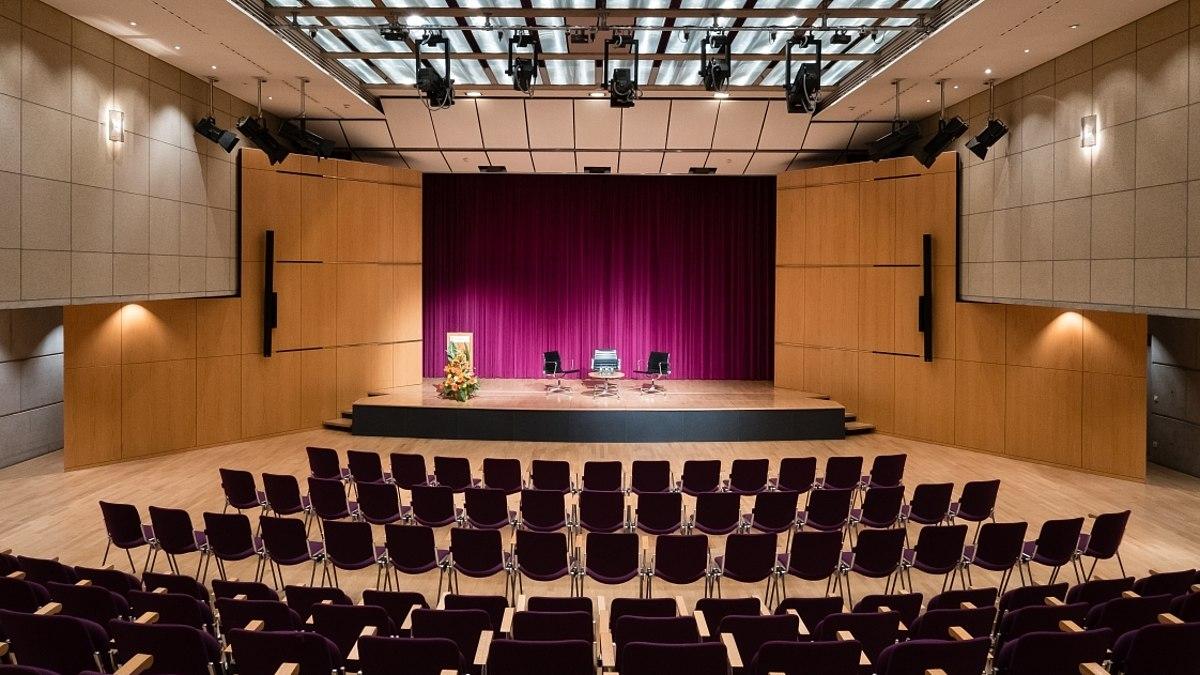 Blick in einen großen Raum mit Stuhlreihen und einer Bühne mit Podium.