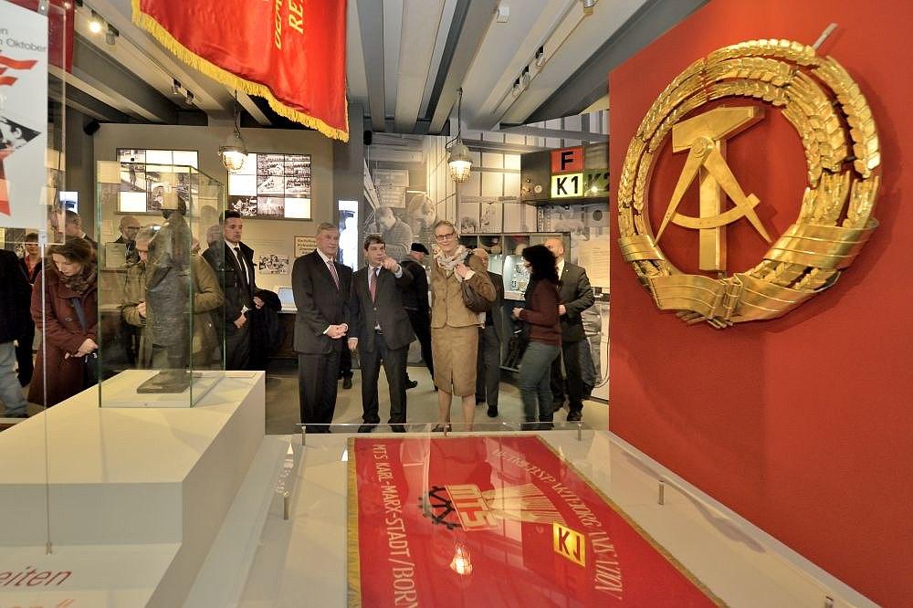 Blick in die Ausstellung mit einem großen goldenen Staatswappen der DDR auf rotem Grund sowie Bundespräsident a.D. Horst Köhler und Stiftungspräsident Hütter
