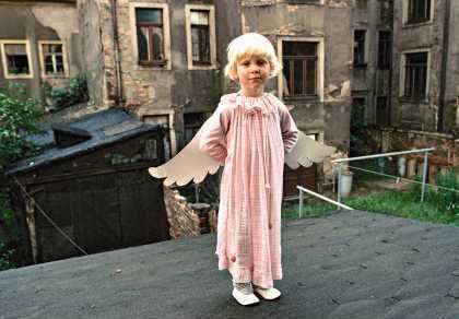 Ein Kind im Engelskostüm in einem Berliner Altbau-Hinterhof 1987
