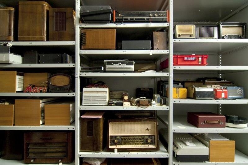 Radios verschiedener Größen und Materialien stehen in einem Metallregal.