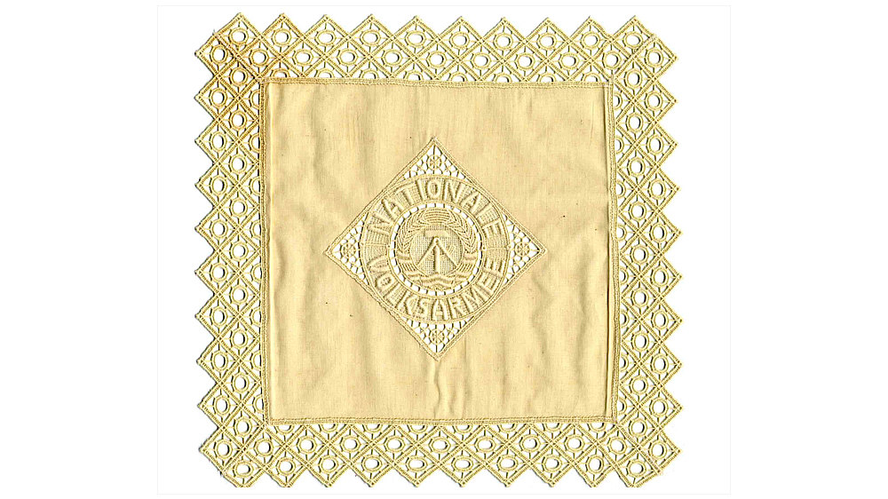 Bräunlich-weißes Tuch mit Spitzenumrandung. Im Zentrum gesticktes DDR-Emblem mit Umschrift: 'Nationale Volksarmee'.