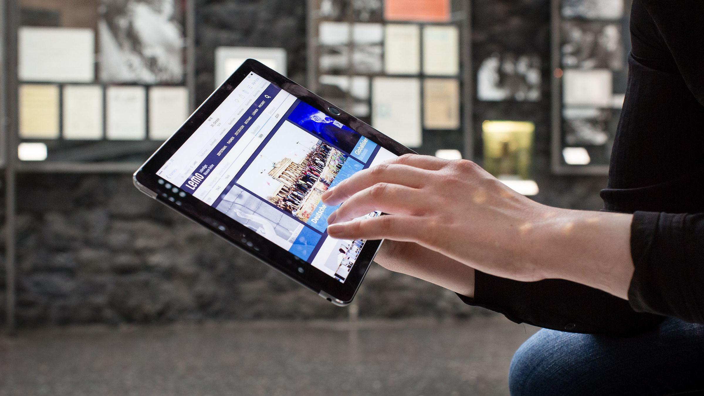 Dateilaufnahme, ein Museumsbesucher im Haus der Geschichte surft auf dem Tablet im Lebendigen Museum Online LeMO
