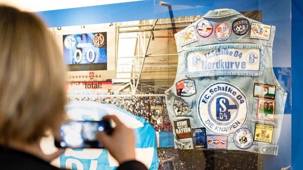 Eine Besucherin fotografiert Objekte zu Schalke 04.