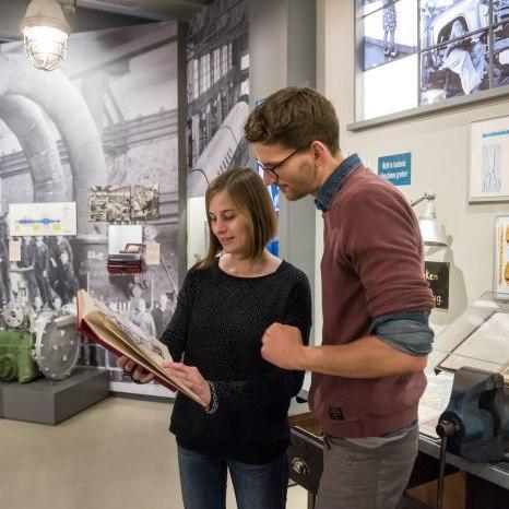 Besucher lesen in einem Brigadebuch in der Dauerausstellung