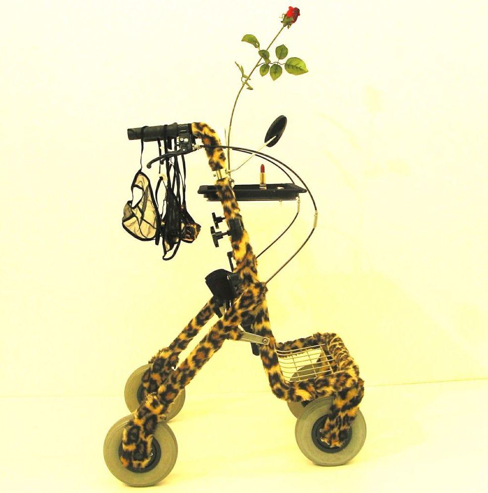 Ein Rollator ist mit einem Stoff aus Tigerfell umwickelt, an den Griffen hängen Dessous mit Tigermuster, an der linken Seite des Rollators steckt eine rote Rose