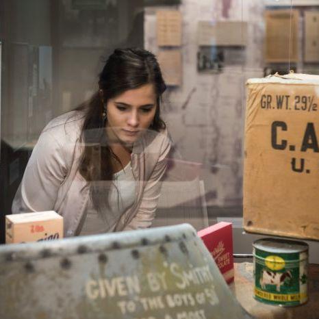 Eine Besucherin betrachtet Objekte zum Thema 'Care-Paket' in der Dauerausstellung