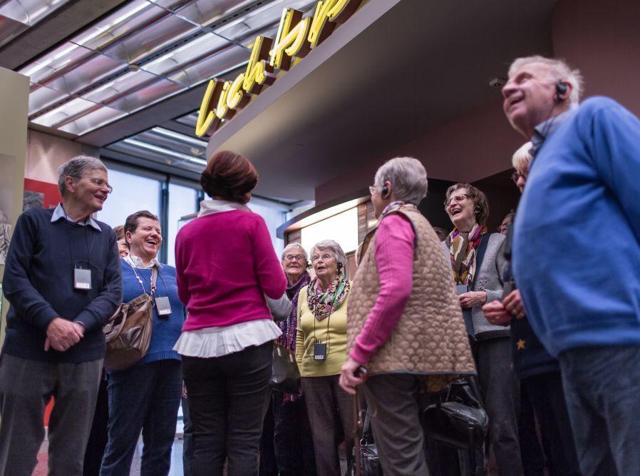 Eine Gruppe Senioren steht vor dem Kino in der Dauerausstellung in Bonn