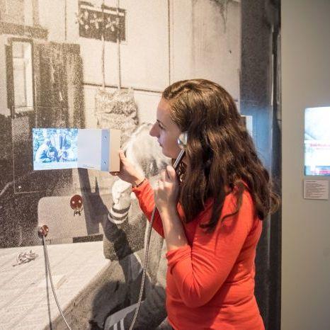 Eine Besucherin betrachtet einen Film in der Dauerausstellung