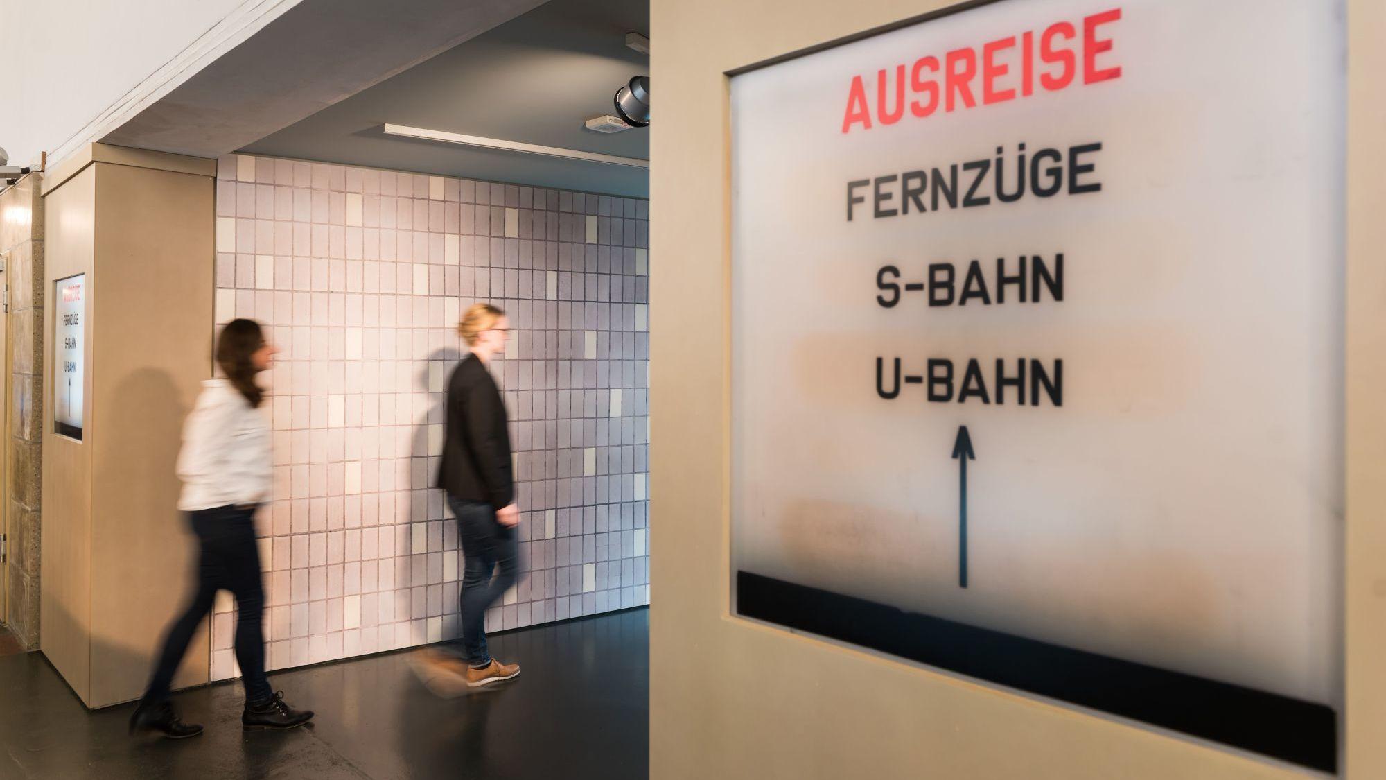 Im Vordergrund ein Schild mit den Worten Ausreise, Fernzüge, S-Bahn, U-Bahn, im Hintergrund gehen zwei junge Frauen in einen Gang
