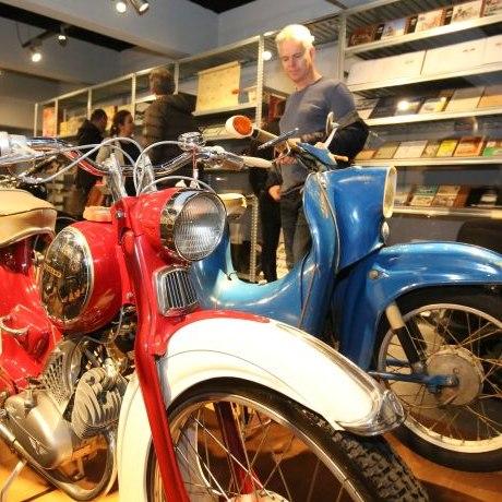 Ein Mann im Hintergrund sieht sich zwei Motorräder im Vordergrund an, eine leuchtend rote Zündapp und eine blaue Maschine.