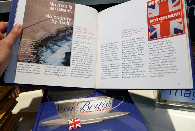 """Aufgeschlagenes Buch zur Wechselausstellung """"Very British. Ein deutscher Blick"""", darunter geschlossenes Buch mit blauem Cover und weißer Teetasse."""