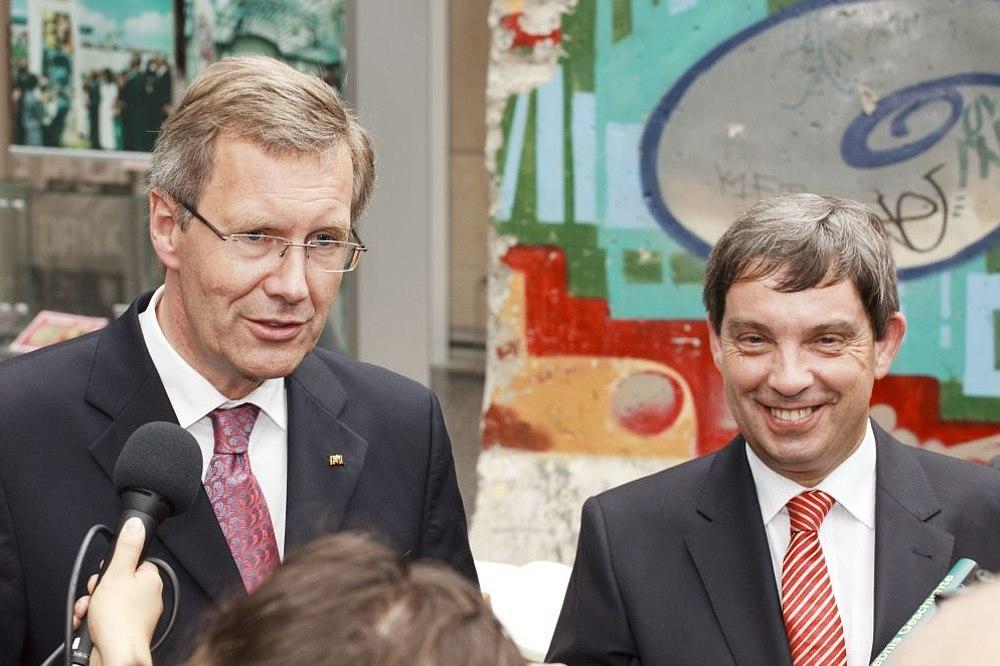 Der damalige Bundespräsident Wulff und Stiftungspräsident Hütter, im Hintergrund Bauteile der Berliner Mauer mit Graffiti, im Vordergrund Mikrofone