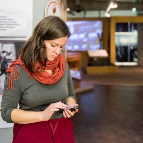 Eine Besucherin blickt auf ihr Smartphone in der Dauerausstellung in Leipzig
