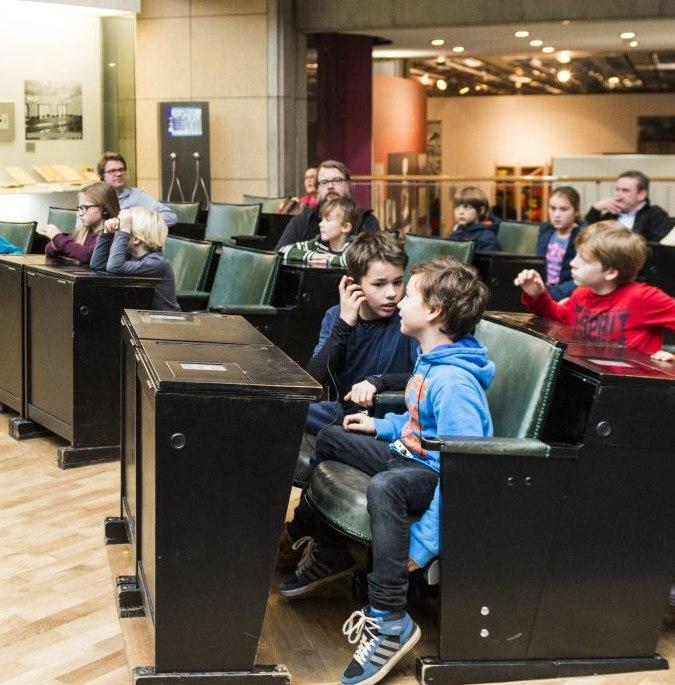 Kinder sitzen im Bundestagsgestühl im Haus der Geschichte