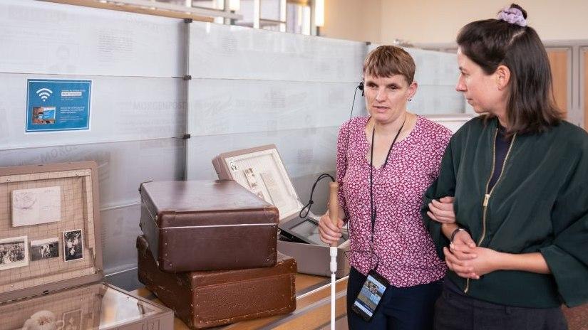 Eine Besucherin mit Blindenstock hört den AudioGuide und geht mit einer Begleiterin durch die Ausstellung