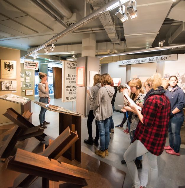 Eine Gruppenbegleiterin führt eine Gruppe durch die Dauerausstellung in Leipzig