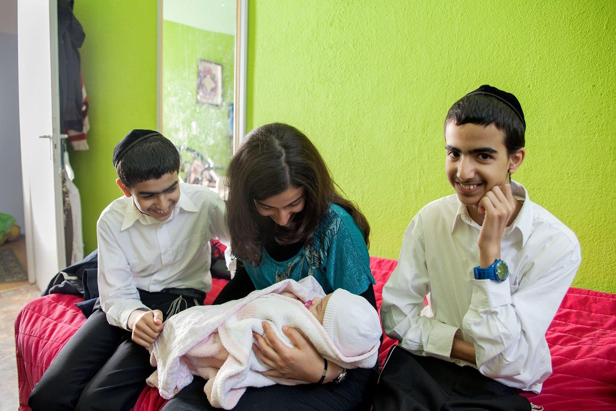 Zwei lächelnde Jungen mit Kippa und Hemd sitzen auf einem Bett, zwischen ihnen eine Frau, die sich über ein Baby beugt.