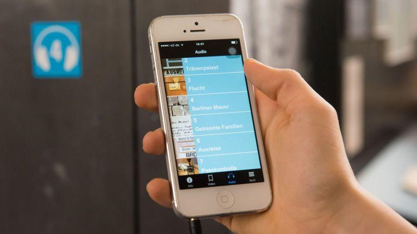 Eine Hand hält die Audioguide-App