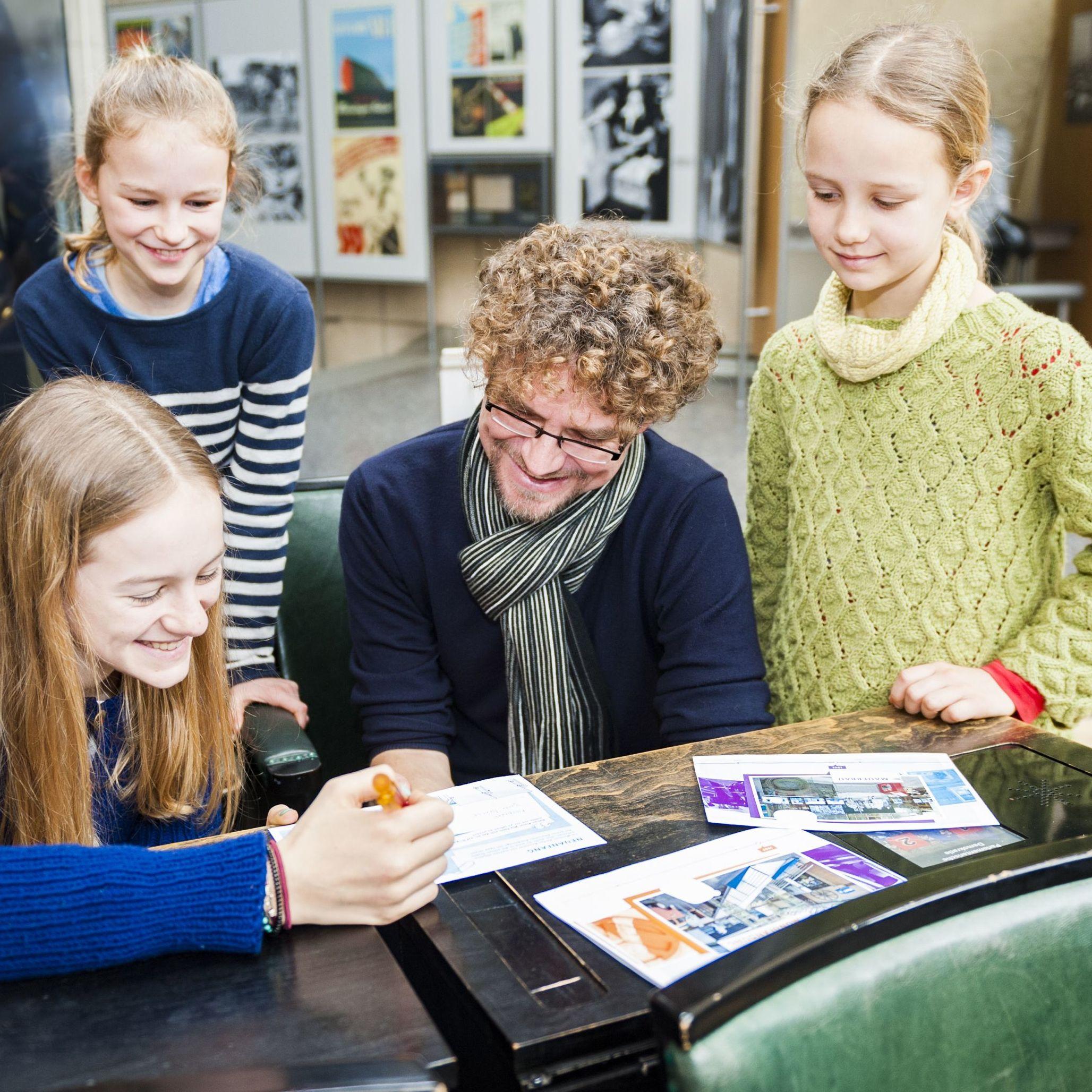 Familie im Bundestagsgestühl im Haus der Geschichte mit museumspädgagogischer Familientour