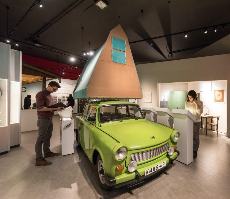 Besucher am Trabi in der Dauerausstellung