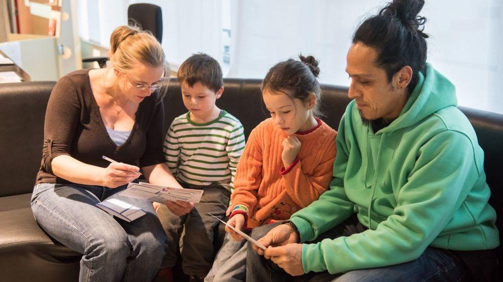 Eine Familie sitzt mit Materialien im Museum