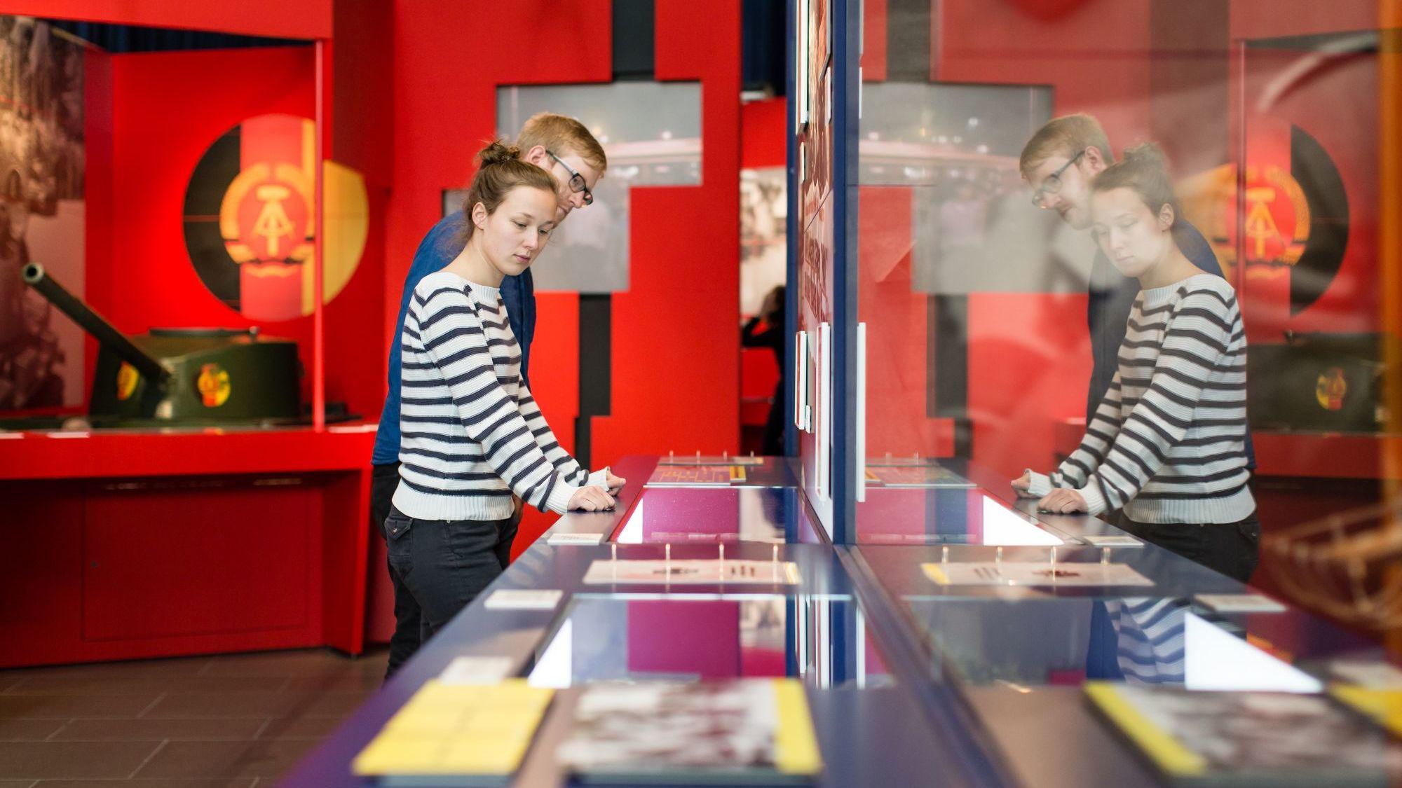 Blick in einen Ausstellungsraum mit einer großen Längsvitrine im Vordergrund und roter Ausstellungsarchitektur im Hintergrund mit DDR- Wappen und einem Kinder-Panzer. Eine junge Frau und ein junger Mann sehen sich die Objekte in der Vitrine an