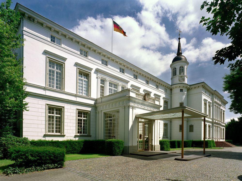 Ein schräger Blick auf die Front des weißen Gebäudes mit einem Türmchem, einem vorgelagerten Eingang und einer Deutschlandflagge auf dem Dach