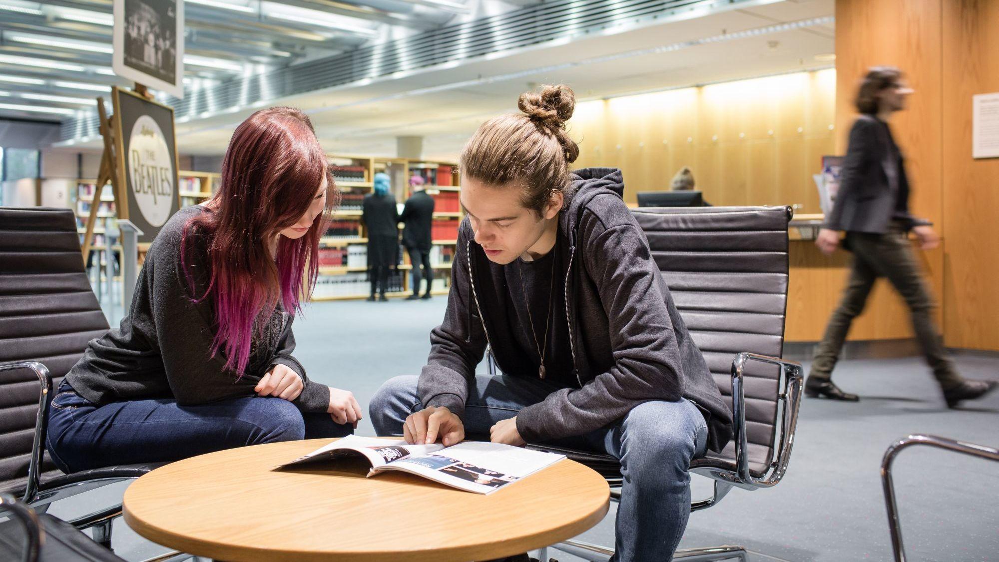 Besucher im Informationszentrum sehen sich eine Zeitschrift an.